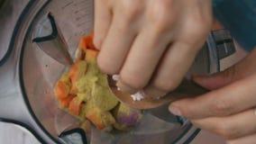 Le mani femminili aggiungono il sale himalayano rosa nel miscelatore per cucinare la salsa di verdure Vista superiore, vegano ed  stock footage