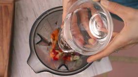 Le mani femminili aggiungono l'acqua pura nel miscelatore per cucinare la salsa di verdure Vista superiore, vegano ed alimento ve video d archivio