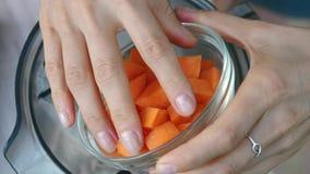 Le mani femminili aggiungono la carota nel miscelatore per cucinare la salsa di verdure Vista superiore, vegano ed alimento veget stock footage