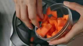 Le mani femminili aggiungono la carota nel miscelatore per cucinare la salsa di verdure Vista superiore, vegano ed alimento veget video d archivio