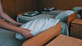 Le mani femminili battono con attenzione un cuscino nella stanza del ` s dei bambini stock footage