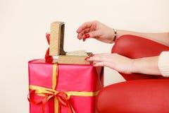 Le mani femminili che aprono il contenitore di regalo dorato con il gioiello imperla Fotografie Stock