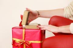 Le mani femminili che aprono il contenitore di regalo dorato con il gioiello imperla Fotografie Stock Libere da Diritti