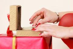 Le mani femminili che aprono il contenitore di regalo dorato con il gioiello imperla Fotografia Stock Libera da Diritti