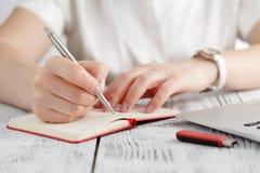 Le mani femminili con il manicure sopra le pagine del taccuino tengono una penna Immagine Stock