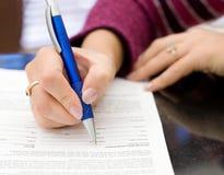 Le mani femminili con una matita scrivono su un documento Fotografia Stock