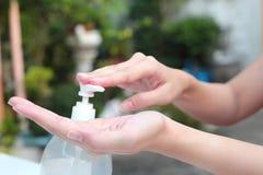Le mani femminili facendo uso dell'erogatore della pompa del gel lavano il prodotto disinfettante della mano Fotografia Stock