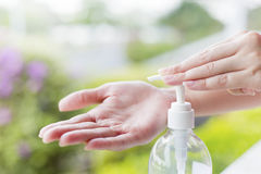 Le mani femminili facendo uso di lavaggio passano l'erogatore della pompa del gel del prodotto disinfettante Fotografie Stock