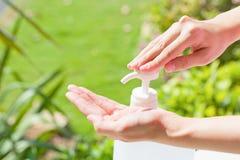 Le mani femminili facendo uso di lavaggio passano l'erogatore della pompa del gel del prodotto disinfettante Immagine Stock Libera da Diritti