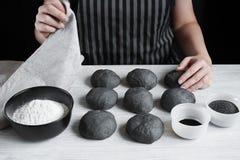 Le mani femminili hanno coperto i panini neri crudi Fotografia Stock