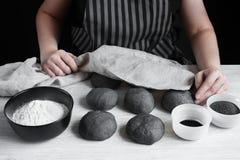 Le mani femminili hanno coperto i panini neri crudi Fotografie Stock Libere da Diritti
