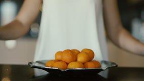 Le mani femminili hanno messo i mandarini in un piatto video d archivio