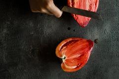 Le mani femminili hanno tagliato il pomodoro di cimelio del cuore del toro organico Superfood Fotografie Stock Libere da Diritti