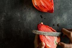 Le mani femminili hanno tagliato il pomodoro di cimelio del cuore del toro organico Superfood Fotografia Stock