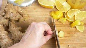 Le mani femminili incidono la radice dello zenzero dei pezzi per una bevanda fatta dall'agrume fatto a mano con lo zenzero 4K stock footage