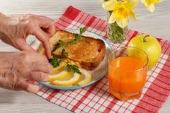 Le mani femminili indicano l'alimento di prima colazione su un piatto Pane tostato con l'estremità Fotografia Stock