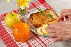 Le mani femminili indicano l'alimento di prima colazione su un piatto Pane tostato con l'estremità Fotografia Stock Libera da Diritti