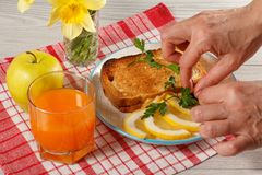 Le mani femminili indicano l'alimento di prima colazione su un piatto Pane tostato con l'estremità Immagini Stock Libere da Diritti