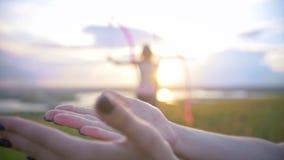 Le mani femminili libera la farfalla davanti agli esercizi della donna con nastro adesivo relativo alla ginnastica al tramonto video d archivio