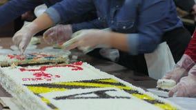 Le mani femminili nel taglio bianco dei guanti agglutinano nei pezzi, un ossequio per gli ospiti al centro commerciale, dolci di  archivi video