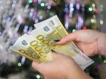 Le mani femminili pensano gli euro contanti che spostano da corpo a corpo le decorazioni di Natale sull'albero di Natale Fotografia Stock