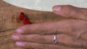 Le mani femminili prendono a taglio il peperoncino rosso piccante dal tagliere Vista superiore Vegano ed alimento vegeterian stil video d archivio