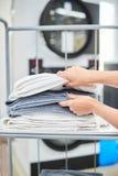 Le mani femminili prendono un asciugamano pulito dallo scaffale Fotografie Stock