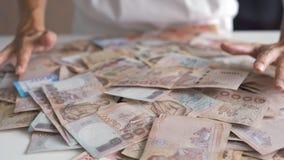 Le mani femminili raccolgono molti soldi su una tavola bianca, le banconote tailandesi, banconote russe fotografia stock