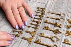 Le mani femminili scelgono una chiave d'annata su un fondo di legno leggero Fotografie Stock