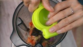 Le mani femminili schiacciano la calce nel miscelatore per cucinare la salsa di verdure Vista superiore, vegano ed alimento veget stock footage