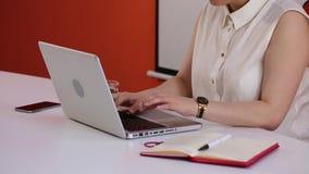 Le mani femminili scrive sul computer portatile in ufficio con tè, il telefono ed il taccuino vicino lei archivi video