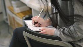 Le mani femminili scrivono rapidamente il testo in un taccuino Lezione sulla correzione o sul trucco del sopracciglio Giovane don stock footage