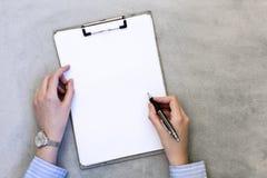 Le mani femminili stanno prendendo le note su fondo grigio fotografia stock