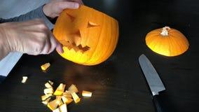 Le mani femminili stanno scolpendo una zucca di Halloween video d archivio