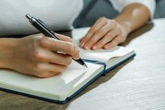 Le mani femminili stanno scrivendo in un taccuino immagine stock