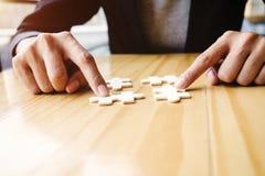 Le mani femminili su una scrivania di legno selezionano il puzzle Fotografia Stock