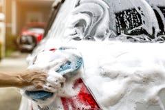 Le mani femminili tengono con l'automobile blu di lavaggio della spugna Fotografia Stock