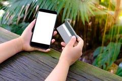 Le mani femminili tengono e per mezzo del telefono cellulare dello smartphone con lo schermo e la carta di credito in bianco o vu immagine stock libera da diritti
