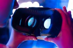 Le mani femminili tengono i vetri della cuffia avricolare del vr 3d 360 alla luce al neon futuristica, fine su immagine stock