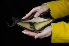 Le mani femminili tengono una borsa da cui ha versato le monete, una finanza nera del fondo immagine stock