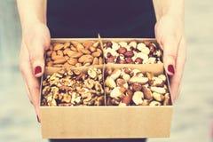 Le mani femminili tengono una scatola dei dadi e dei frutti secchi Immagine Stock