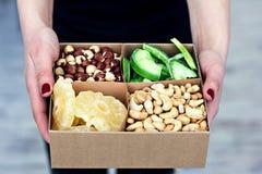 Le mani femminili tengono una scatola dei dadi e dei frutti secchi Immagini Stock Libere da Diritti