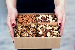 Le mani femminili tengono una scatola dei dadi e dei frutti secchi Fotografie Stock