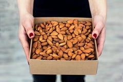 Le mani femminili tengono una scatola dei dadi e dei frutti secchi Immagine Stock Libera da Diritti