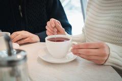 Le mani femminili tengono una tazza bianca di tè sui precedenti di un man& x27; mani di s Fotografia Stock Libera da Diritti