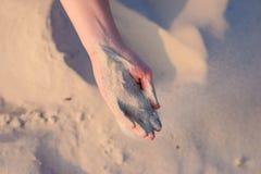 Le mani femminili versano la sabbia sulla terra fotografie stock libere da diritti