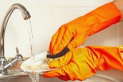 Le mani in guanti lavano i piatti sotto acqua corrente in cucina Fotografie Stock Libere da Diritti