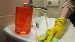 Le mani in guanti lavano il bagno del lavandino video d archivio