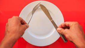 Le mani hanno messo il coltello della forcella all'angolo acuto sul piatto sulla Tabella rossa video d archivio