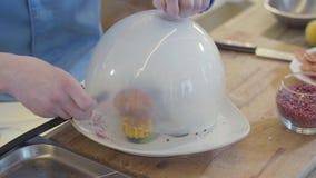 Le mani hanno messo il ghiaccio secco dal tubo ad un grande piatto con la copertura di vetro cucina molecolare video d archivio